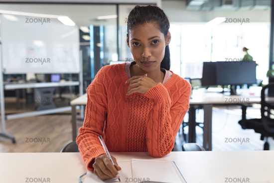 Portrait of mixed race female creative worker sitting at desk looking at camera