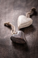 Black and white: two wooden hearts on wooden background