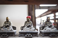 Small bronze buddhist statues with coin and hat offerings in Daisho-in temple in Miyajima, Hiroshima, Japan