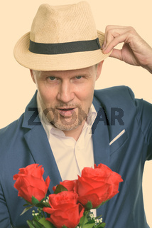 Close up of mature businessman holding hat and red roses ready for Valentine's day