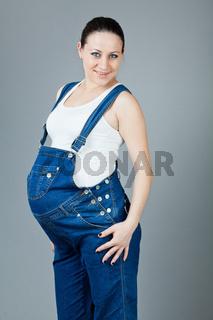 Portrait of pregnant brunette woman on grey backgr