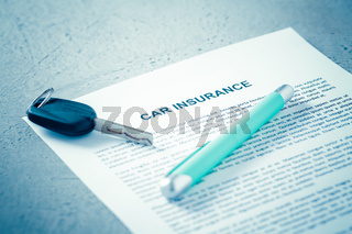 Concept of car insurance - car policy with car keys on blue tone