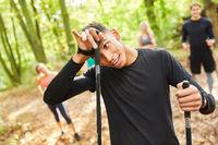 Junger Mann schwitzt nach dem Nordic Walking