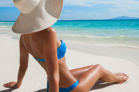 Woman in sun hat sitting on beach