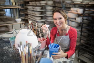 Portrait of female potter holding color tube