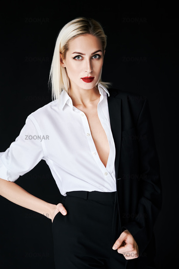 Young stylish woman wearing classic men's suit posing on black studio background
