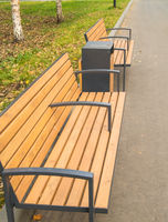 Modern wooden bench and urn in the autumn park, vertical photo