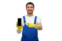 happy male worker or cleaner showing smartphone