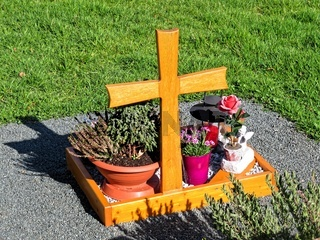 A new grave with simple wooden cross and flowers.