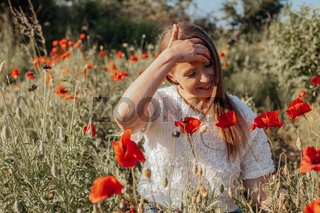Young beautiful woman in wild flowers summer field