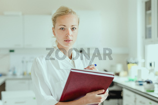 Portrait of young, confident female health care professional taking notes during inventory in scientific laboratory or medical doctors office