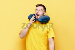 Tired young man yawning on yellow background