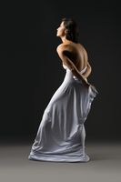 Slim graceful woman wrapped in white cloth in studio