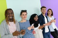 diverse teenagers use mobile devices while posing for a studio photo in front of a pink background
