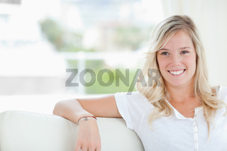 A woman smiling as she sits on the couch and looks to the side
