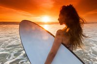 Woman with surfboard on tropical beach