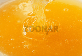 Close up pouring fresh fluid honey in bowl