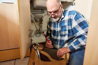 Klempner mit Werkzeugtasche vor der Spüle in der Küche