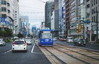 Hiroshima downtown with new tram on electric railway in busy street, Hiroshima, Japan