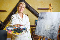 Satisfied female artist posing near new picture next to easel.