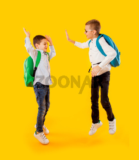 Jumping emotional schoolboys on the yellow background