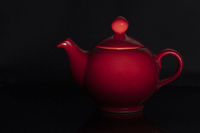 Teapot of red color of the classical form on a black background.