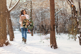 Brunette woman with Christmas wreath on snow