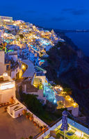 Brightly lit Fira town in Santorini island at dusk