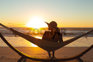 Mixed race woman on beach holiday sitting in hammock during sunset