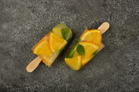 Orange and mint ice cream popsicles on table