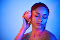Pretty afro woman with closed eyes pressed seashell to her ear enjoy and dreams in neon light