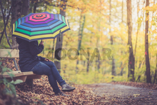 Beautiful girl with umbrella in the forest, autumn time