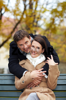 Mann umarmt Frau im Park