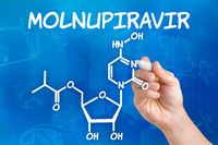 Hand with pen drawing the chemical formula of Molnupiravir