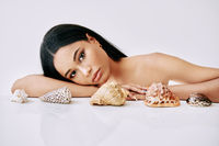 Beautiful african american woman with different seashells on white background