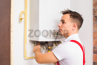 The plumber works with boiler at the kitchen