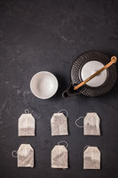 Assorted tea bags with tea pot and cup on black stone background