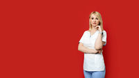 Confident female doctor standing on red background. Young woman intern in medical clothes posing.