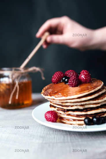 Pancakes with berries and honey on white plate, hand holding spoon in jar