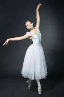 Beautiful girl dances in a ballet dress