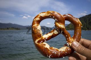 Hand hält eine Brezel am Walchensee