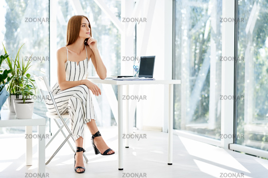 Pretty smiling businesswoman posing in a modern office sitting on her desk