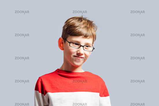 Confused schoolboy in glasses scratching his head