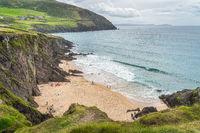 Families relaxing on Coumeenoole Beach hidden between cliffs in Dingle