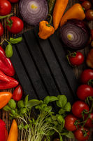 Delicious vegetables served around on the black striped palet