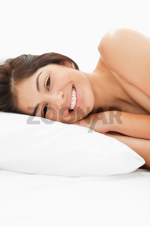 A woman lying on the bed, her head on the pillow, her eyes are open and she is happily smiling