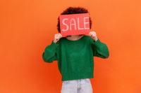Portrait of unknown woman wearing green casual style sweater covering her face with card with sale inscriptions, shopping, discounts.