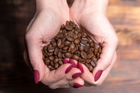 Fresh roasted coffee beans pouring out of cupped woman hands on a wooden background
