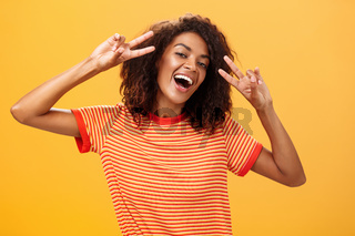 Nobody gonna spoil my perfect mood. Portrait of happy optimistic attractive dark-skinned female model with curly hairstyle tilting head smiling carefree showing peace or victory signs near face