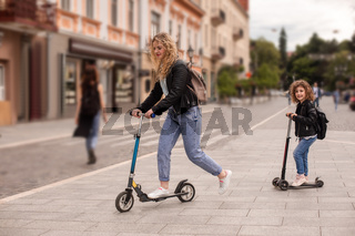 The stylish young mom and daughter are riding scooters